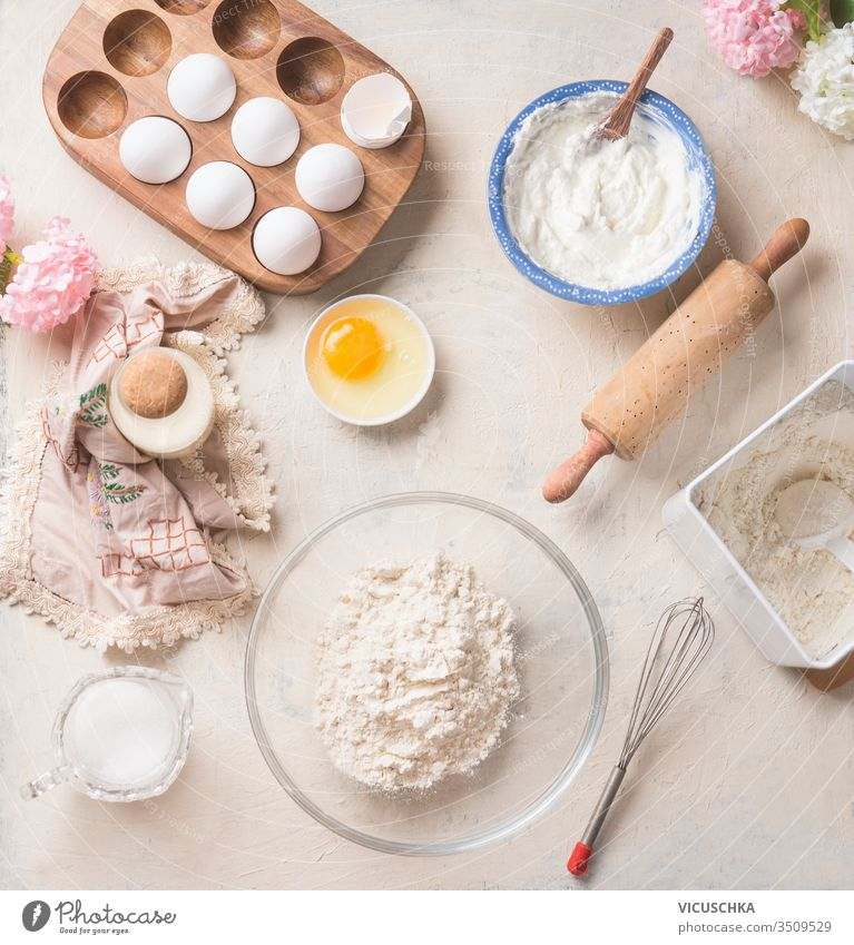 Modern baking background with flour in bowl, eggs and ingredients on white kitchen table background, top view. Home Bake. Recipes to cookies, pie and cake