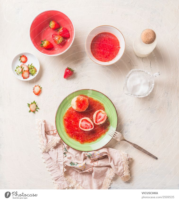 Tasty boiled cottage dumplings stuffed with fresh strawberries. Summer sweet food. breakfast tasty sauce green plate white kitchen table top view summer home