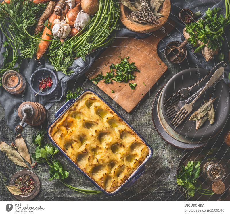 Baked mashed potato in casserole with spoon on dark rustic kitchen table background with ingredients and vintage utensils. Top view. Tasty home cuisine top view