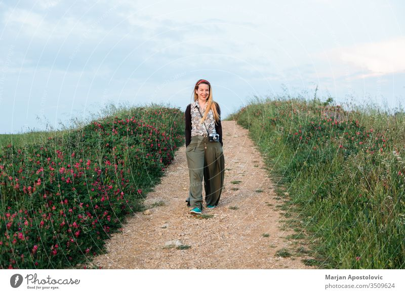 Young female adventurer walking in the fields of Tuscany, Italy adult camera casual cheerful country countryside enjoying europe evening explorer flowers