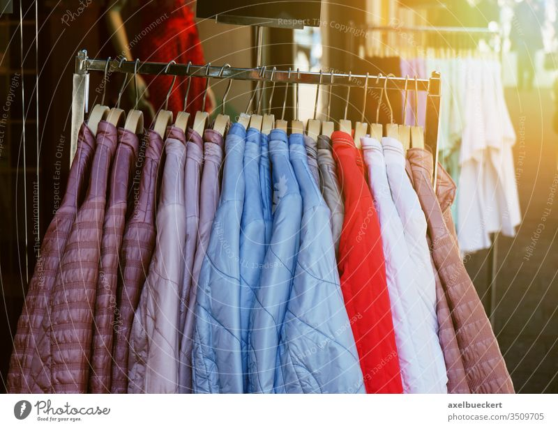 clothes rack with ladieswear spring fashion jackets hanging outside store clothing shop display pastel sun flare light leak retail collection style hanger