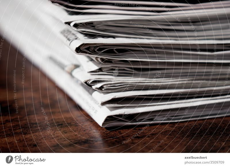 pile of newspapers or papers table desk print media heap stack information press journalism business publication current events recycling recycle reading