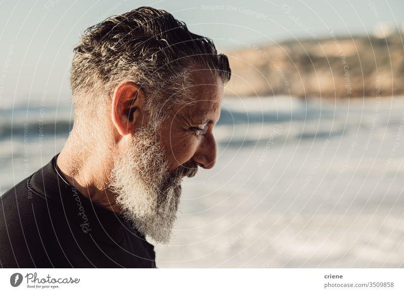 Senior man with long beard smiling at beach senior men vacation surfing adult smile grey hair lifestyle joy sport hobby portrait ocean waves adventure outdoor
