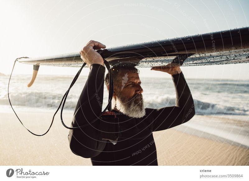 Caucasian Senior man with beard carrying surfboard on his head senior men vacation beach surfing adult grey hair lifestyle sport hobby portrait ocean waves