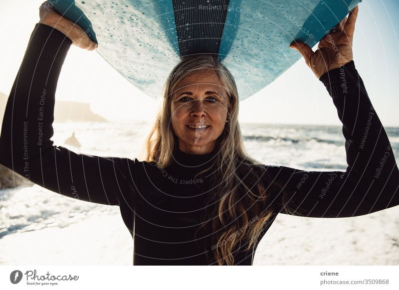 Smiling senior woman carrying surfboard at beach looking at camera women vacation surfing adult smile grey hair lifestyle joy caucasian sport hobby portrait