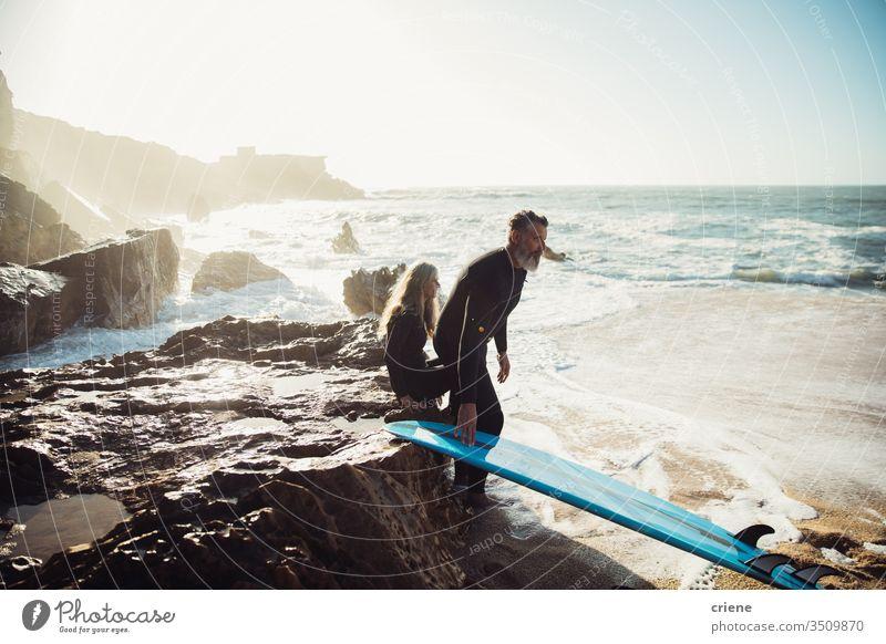 Senior couple sitting together on rocks with surfboards taking a break senior men vacation beach surfing adult beard grey hair lifestyle joy sport hobby