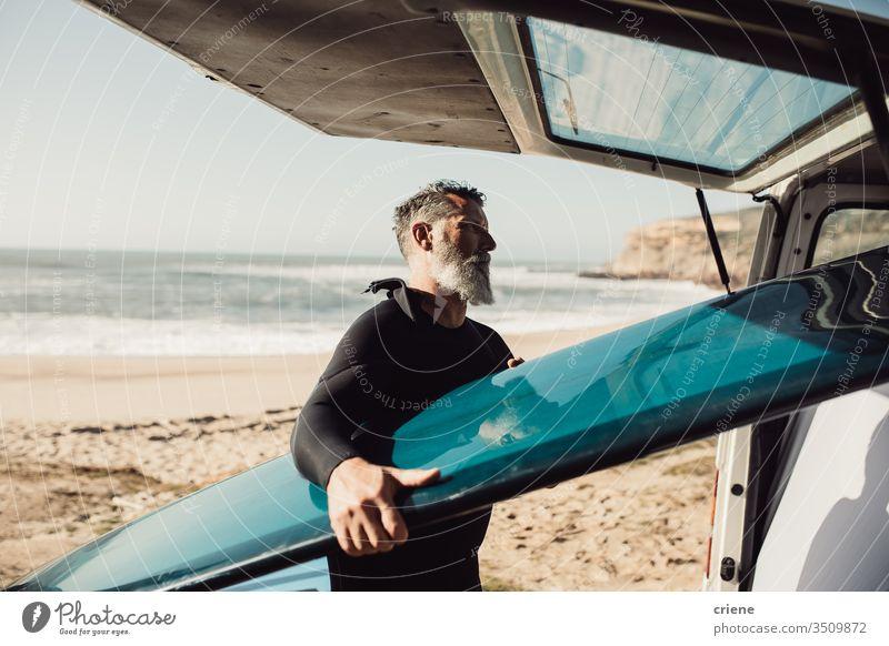 Senior man taking surfboard out of van at beach senior men transport trip vacation surfing adult beard grey hair lifestyle joy hobby