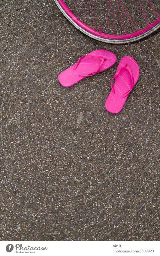 Bright pink flip-flops, standing abandoned on the asphalt of the road in summer, in front of a pink bicycle tire, waiting for their owner. Summer Flip-flops
