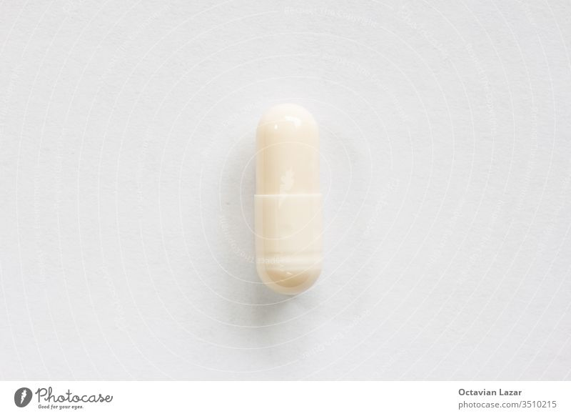 Cream colored medicine soft pill capsule macro close up shot isolated on white surface illness medicament painkiller medication dose closeup hospital background