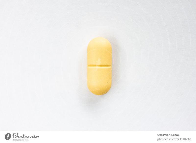 Yellow colored medicine pill capsule macro close up shot isolated on white surface yellow illness medicament painkiller medication dose closeup hospital