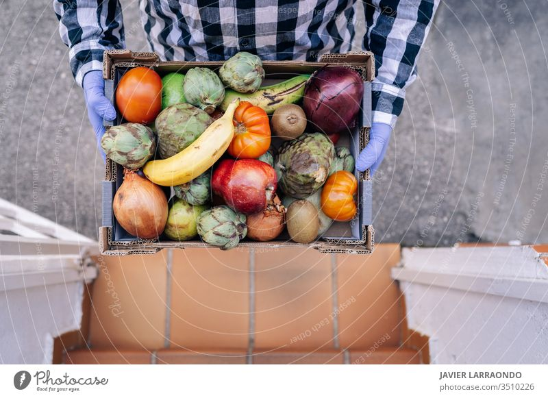 Male volunteer holding a box with vegetables and fruits in a house stairs. Volunteer,lockdown,epidemic concept aid assist assistance charity community