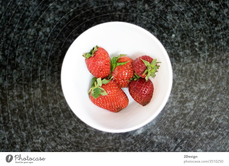 Top view of strawberries over dark marble rural closeup sweet juicy dessert bowl light white vegetarianism fresh nourishment spring season fruit diet berry red