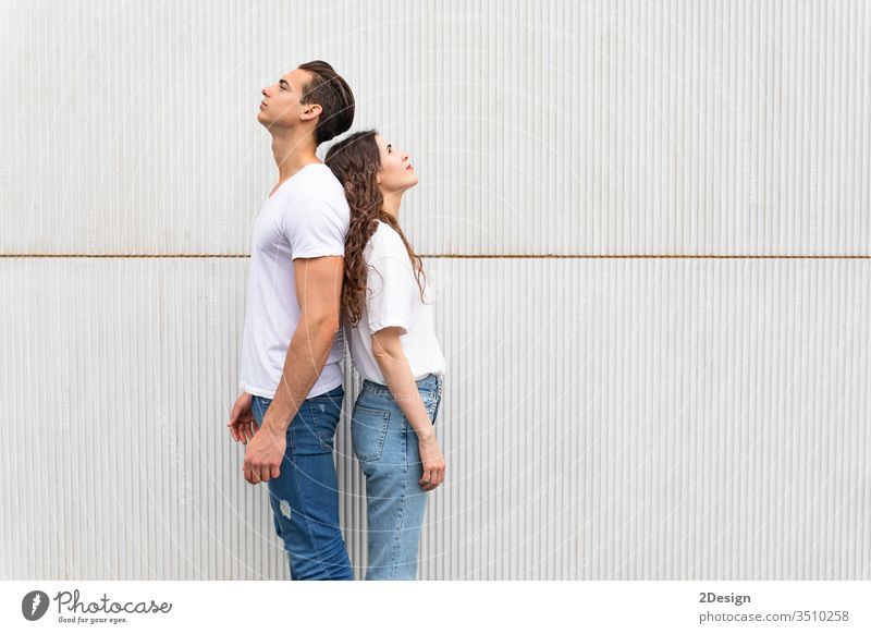 Young couple standing back to back against white urban wall woman young people female girl happy 2 portrait background beautiful casual attire caucasian guy