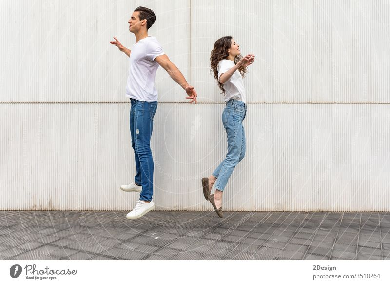 Young couple jumping back to back against white urban wall lifestyle young caucasian woman happy city happiness beautiful girl fun two love summer female