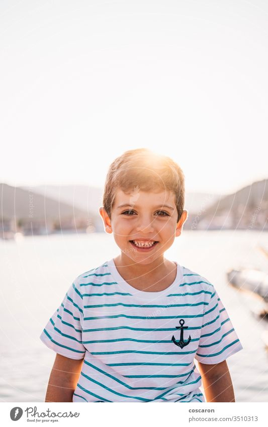 Cute kid smiling at sunset with the sea in the background beach beautiful blue boy bright cheerful child childhood children coast coastline color cute face