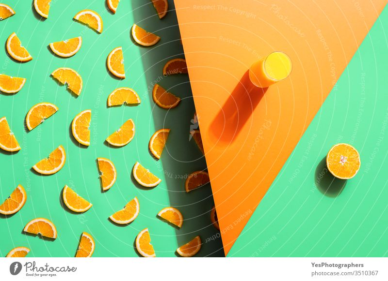 Orange juice glass and orange slices on duotone background. Summer drink beverage bicolor citrus fruits cocktail colorful concentrate detox beverage extract