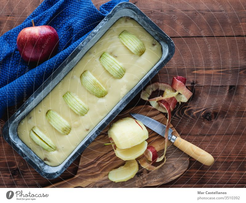 Stuffed mould for baking an apple cake on a dark wooden base. Copy space. Baking concept. Sponge cake raw sweet dessert cake tin pastry food unbaked top view