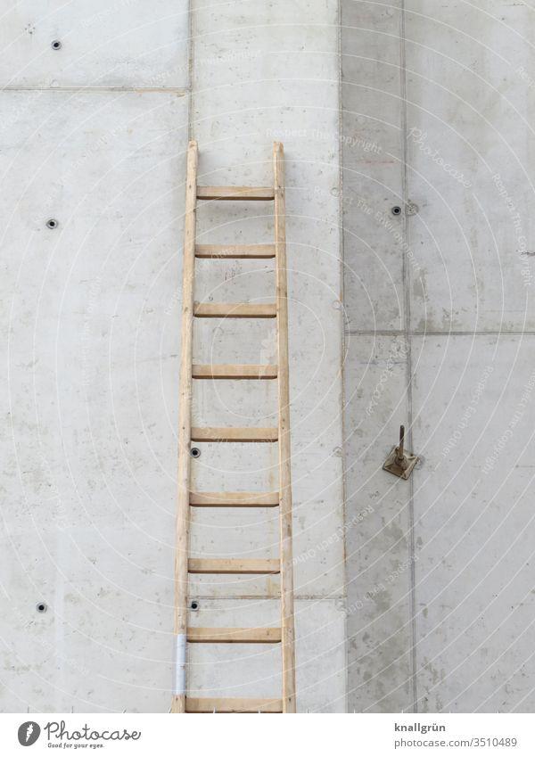 On a construction site a wooden ladder leans against a concrete wall Ladder Concrete wall Construction site Wooden ladder rung ladder Wall (building) Build job