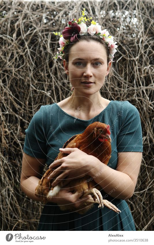 Young woman with a wreath of flowers in her hair stands in the chicken run holding a brown chicken in her arms Central perspective Shallow depth of field Day