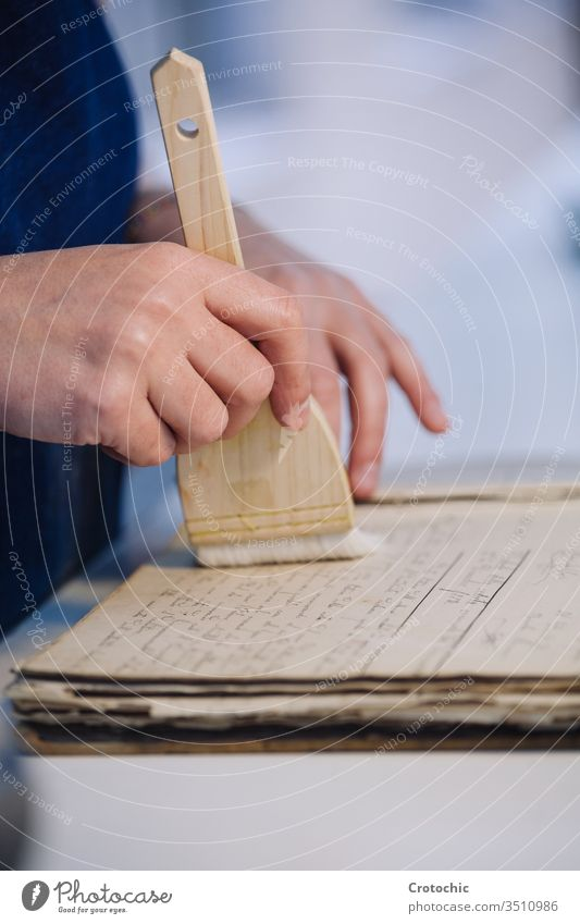 Person cleaning a page of an old book with a brush to repair it ancient hand person worker soft care vertical bookbinding wood handcraft handmade paper printing