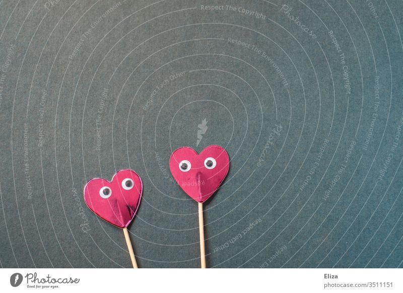Two pink hearts on a stick with eyes that look at each other cuddle two handle peer wobbly eyes In love Love Emotions Blue Pink Red Valentine's Day Couple Heart