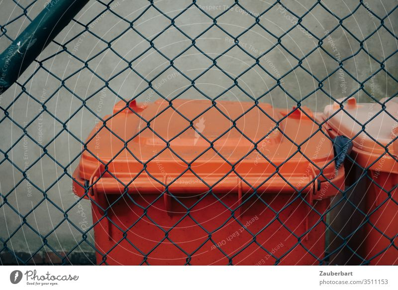 Garbage can in orange behind green wire mesh fence dustbin Orange Wire netting fence Trash Disposal city cleaning Fence little story lid Recycling Plastic