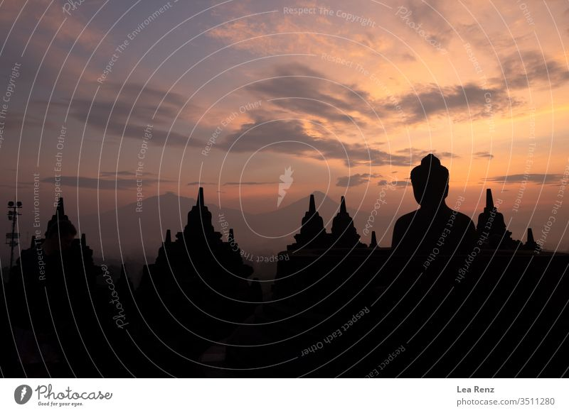 Visiting the Borobudur Temple on Java (Indonesia) for an amazing colorful sunrise. sunset sky silhouette skyline city orange dusk red architecture black