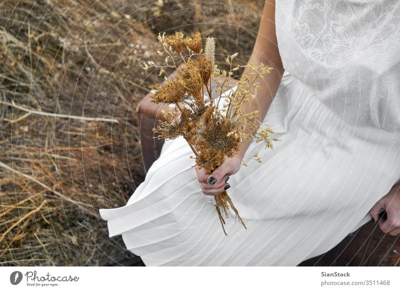 Woman with white dress hold bouquet with dry flowers sun winter brown outdoor people happy portrait travel lifestyle holding hands lady model female concept