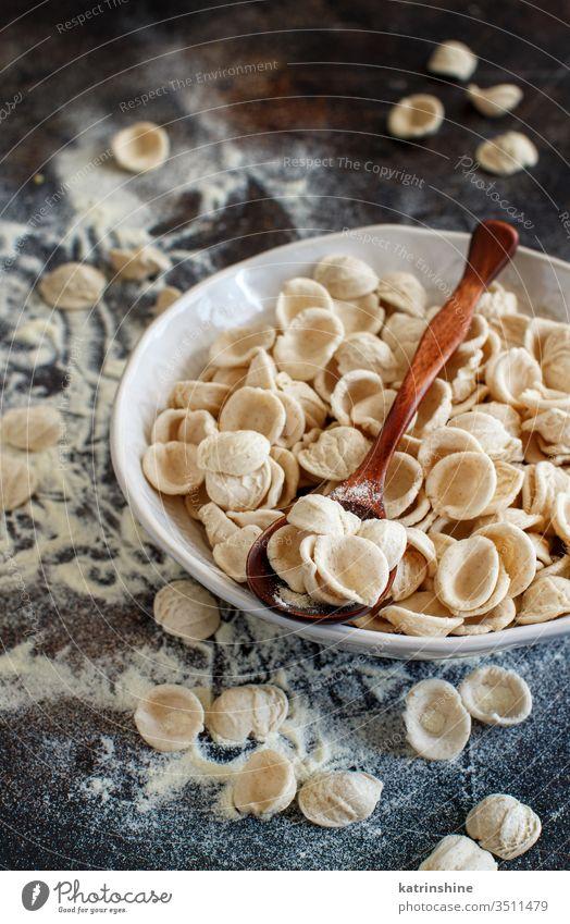 Fresh raw  italian pasta orecchiette apulia fresh dry traditional ingredient close up spoon dark plate diet flour handmade homemade mediterranean organic