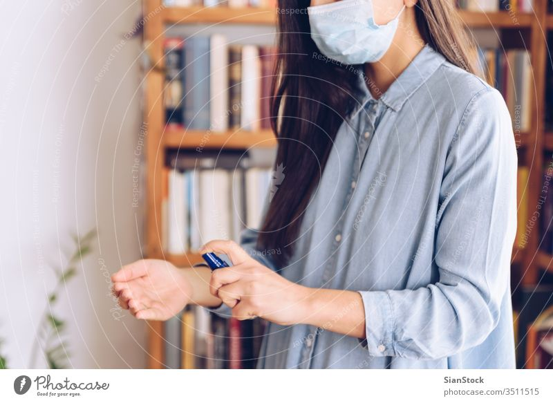 Coronavirus concept. Girl in her home spray with antiseptic her hands for protection from coronavirus. Global call to stay home. covid quarantine gloves