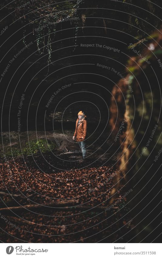 Man alone in a cave Human being Woman cap style stylish Modern Jacket Hipster Yellow Orange Cave grotto conceit somber Loneliness sad on one's own look