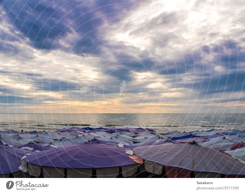 Large umbrella crowded along the beach sky dark cloud cloudy outdoor summer sea blue beauty white holiday travel vacation ocean relax sunlight