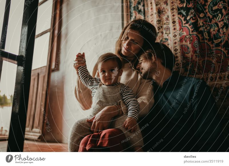 Lovely portrait of cute couple sitting inside home, on the stairs, while rest with their son. Beautiful light entering through the window. interior day calm