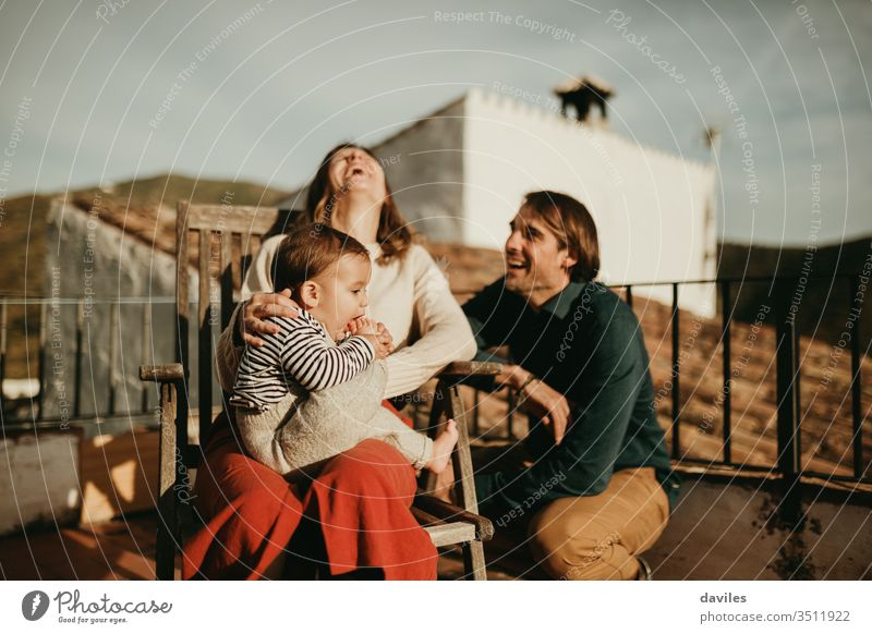 Parents laughing and having fun with their baby son sitting at the home terrace, with beautiful sunset light. real authentic alternative patio cheerful wife