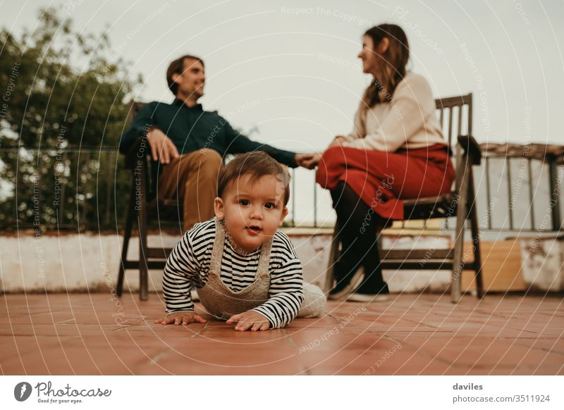 Cute baby infant crawling away from their parents, that are sitting in the background. Baby looks at camera. fatherhood cute eyes house cheerful talking