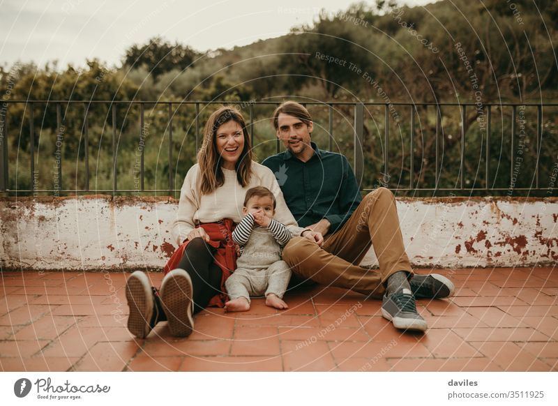 Happy family portrait with man and woman sitting on the floor with their baby at home terrace. real authentic alternative patio cheerful wife carefree backyard