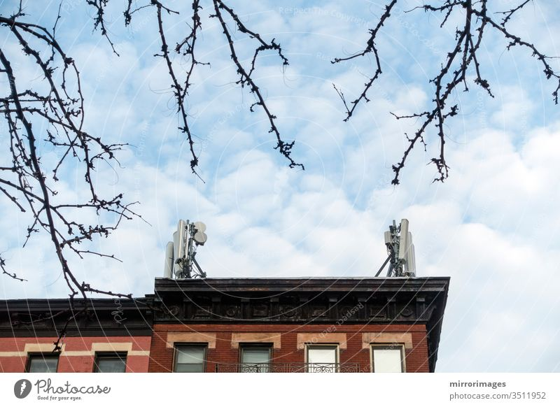 Spring trees, New York buildings with cell phone towers on their roof on a sunny, cold day Architecture Sky no people Building exterior City Repetition Tower
