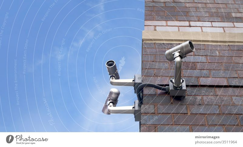 corner of an outdoor brick building with 3 csurveillance camera poiinting in different directions on a beautiful day cctv city control electronic equipment lens