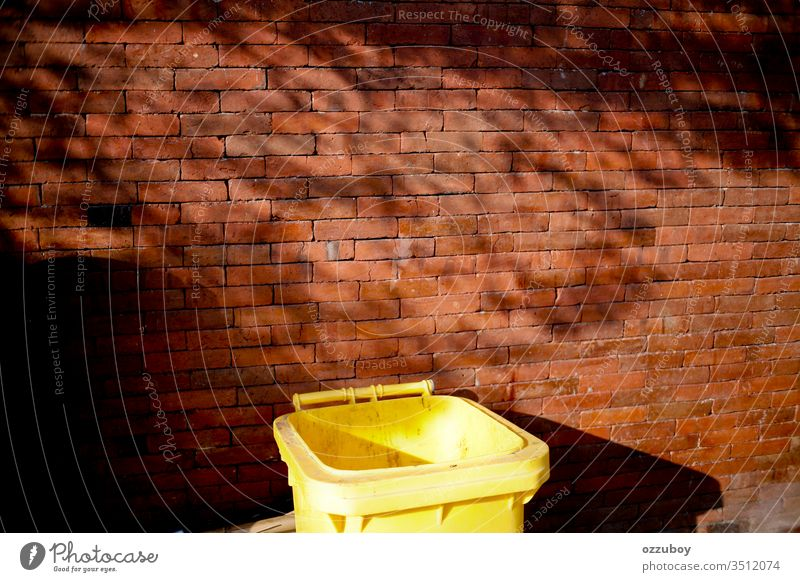 close up garbage bin Wall (building) Brick Brick wall Copy Space Yellow Red Garbage dump garbage can Trash container Shadow simplicity Shadow play Plant
