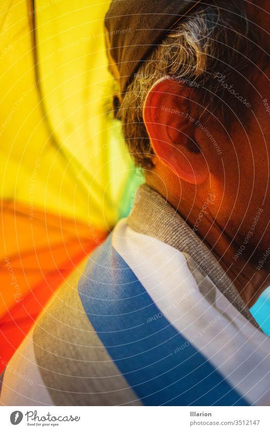 Close up of an old man`s ear with a rainbow umbrella on the foreground Elder Ear Rainbow rainbow colored Rainbow cloth Colour colors colorful Multicoloured