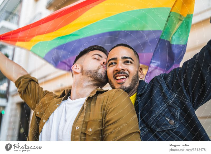 Gay couple embracing and showing their love with rainbow flag. lgbt homosexual freedom gay two partners proud closeness outside diversity support celebrate