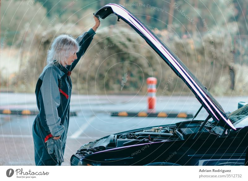 Attractive young blonde female wearing an auto mechanic uniform and repairing the car automobile caucasian vehicle attractive background black blue machine