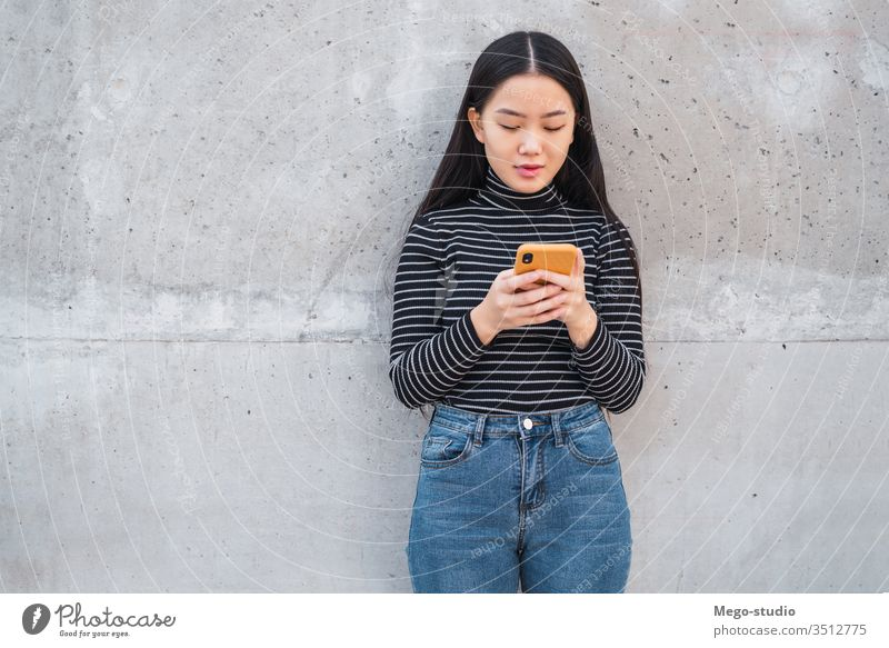 Asian woman using her mobile phone. grey wall asian japanese chinese girl korean cellphone telephone female smart young smartphone lady text people use message