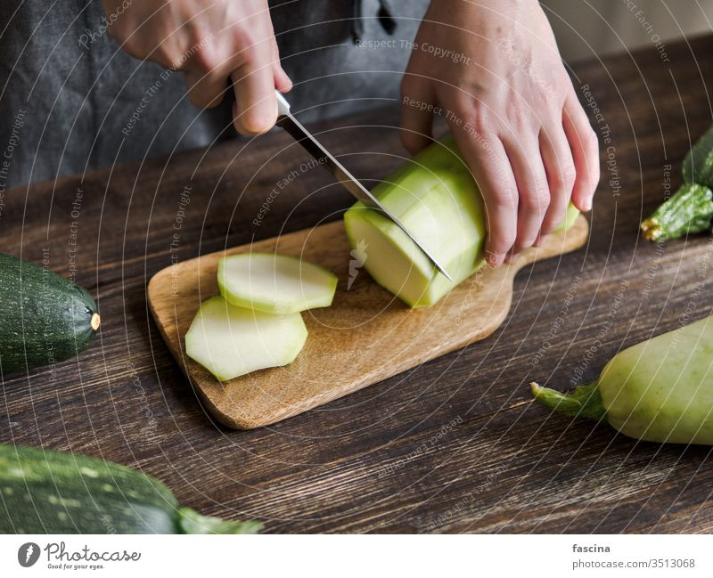 Zucchini harvesting concept. zucchini sliced woman female hand knife cut fresh organic vegetable green ingredient courgette food plant raw summer vegetarian