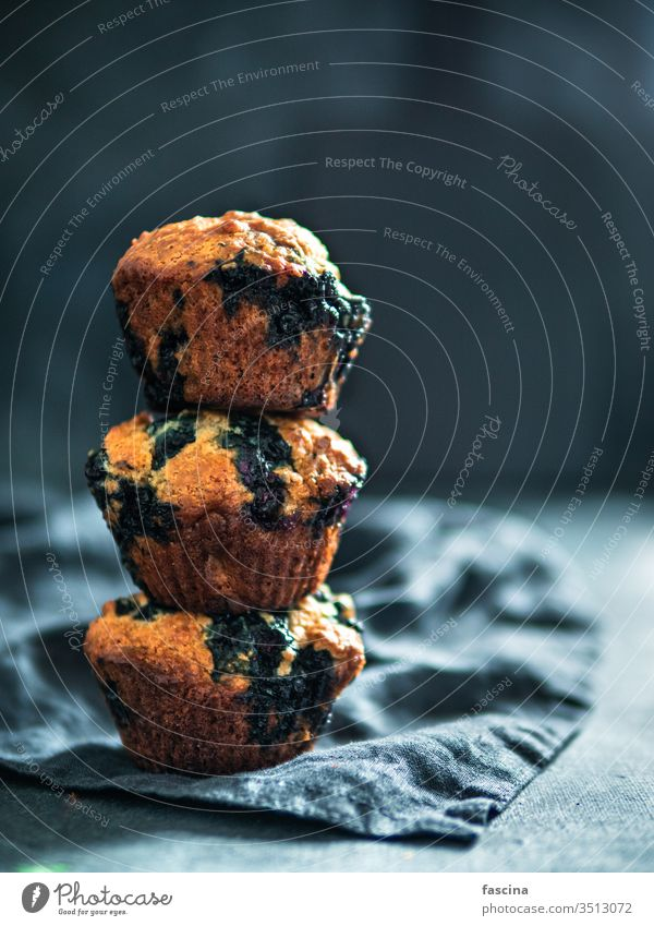 Homemade blueberry muffins on dark background. low calories homemade blueberries muffins three stack nobody top view above vertical food dessert cake snack