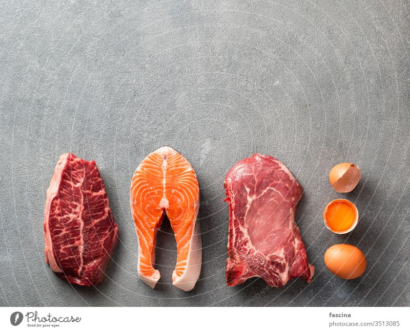 Carnivore or keto diet, zero or low carb concept, top view carnivore paleo lay flat steak beef pork rib eye eggs gray stone background fish meat ingredients raw