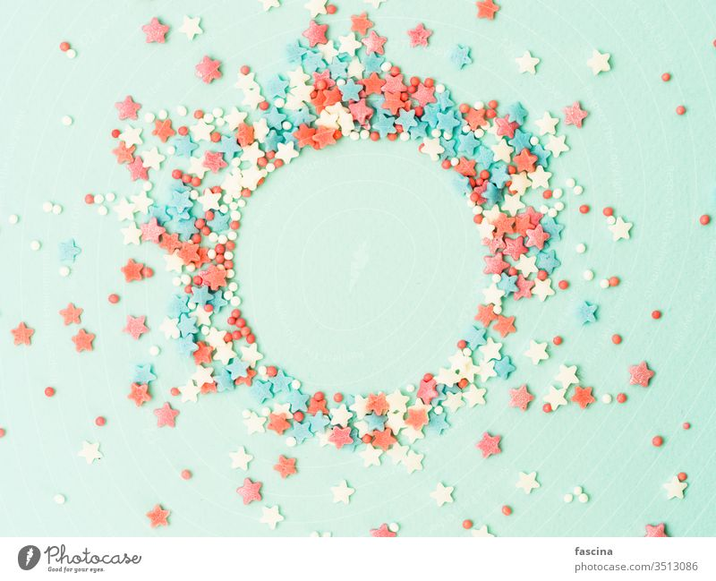 Sprinkles in round spahe on blue, copy space sprinkles top view isolated pastel stars dots circle shape flat lay center design background above text bakery cake