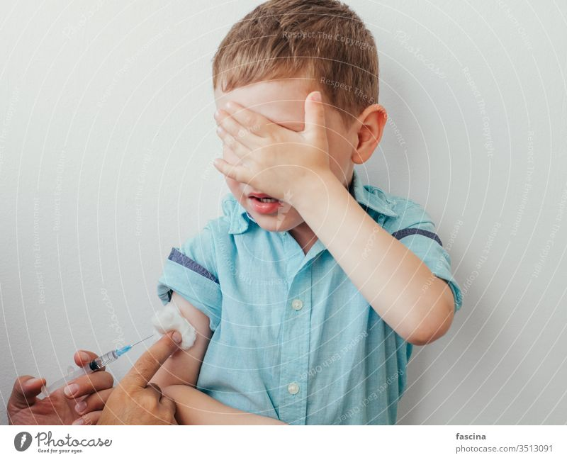 Little boy is afraid to vaccinate little vaccine caucasian injection kid white covered eyes blue shirt hand during vaccination children concept pediatrician