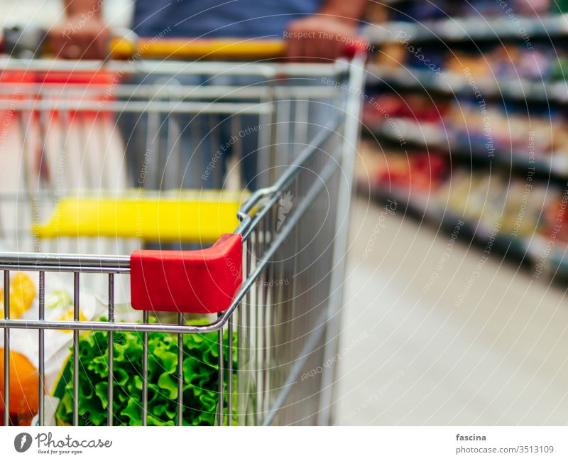 shopping cart in supermarket aisle, copy space trolley grocery man hands latin caucasian hold food store retail shelf customer hypermarket consumer consumerism