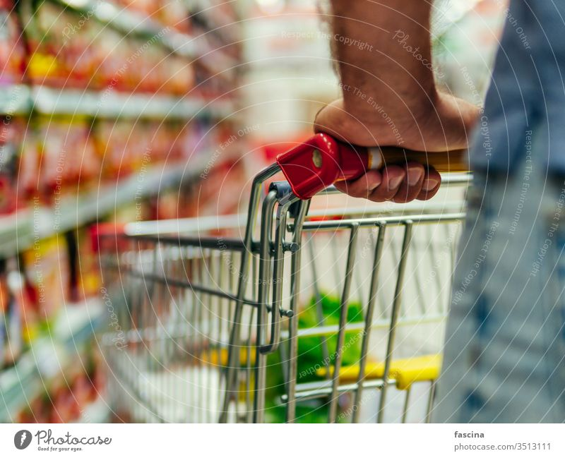shopping trolley in supermarket aisle, copy space grocery cart man hands latin caucasian hold food store retail shelf customer hypermarket consumer consumerism